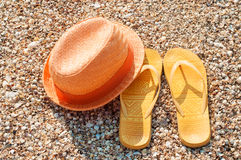 Bright summer hat and sandals on the beach Royalty Free Stock Photos