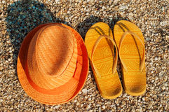 Bright summer hat and sandals on the beach Royalty Free Stock Photo
