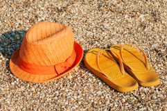 Bright summer hat and sandals on the beach Stock Photography