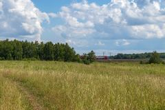 Bright summer landscape with blue sky. Country road through a field in the countryside. Moscow region, Russia. Bright summer landscape with blue sky. Country stock image