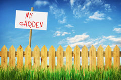 Bright summer landscape with wooden fence and tablet My garden Royalty Free Stock Image
