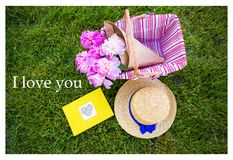 Bright summer picnic. Basket with beautiful flowers and a straw hat, book on a plaid-inscription I love you Stock Photos