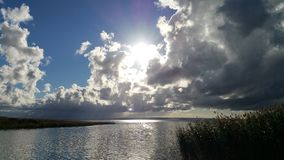 Bright sun above dark clouds over a lake Stock Photography