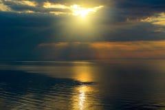 Bright sun in black clouds over ocean Stock Photo