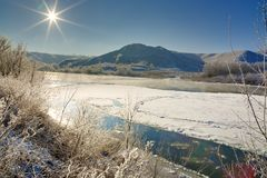Bright sun in the cloudless sky. Freezing river. From the hilly banks and large ice floes Royalty Free Stock Photo