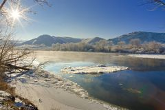 Bright sun in cloudless sky. Freezing river from the hilly b. Bright sun in the cloudless sky. Freezing river from the hilly banks and large ice floes Stock Photo