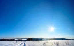 The bright sun descends over the Ukrainian countryside with magnificent rays. The bright sun goes down in winter over the Ukrainian countryside with magnificent Royalty Free Stock Image