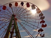 Bright sun and ferris wheel in spring. stock photos
