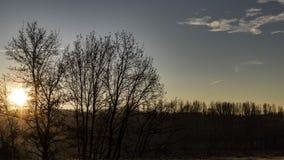 Bright sun flare shining over a blue dusk sky royalty free stock photography