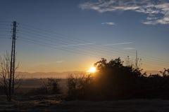Bright sun flare shining over a blue dusk sky royalty free stock image