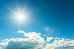 Bright sun and flare. A view of the sky with the bright sun over the sky with a lens flare Royalty Free Stock Images
