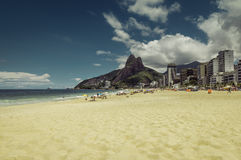 Bright sun on Ipanema Beach with people relaxing against Rio de Janeiro skyline Royalty Free Stock Image