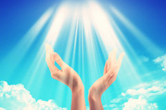 Bright sun light between two hands over blue sky Royalty Free Stock Photography