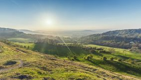 Green Hills at Spring in United Kingdom. Bright sun over Cotswold Way Valley. British landscape at spring from Barrow Wake Viewpoint in England stock images