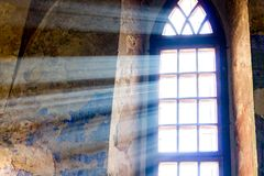 The bright sun rays penetrate the window of the old castle_. The bright sun rays penetrate the window of the old castle royalty free stock photos