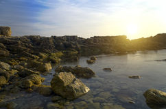 Bright sun and the rocky beach Royalty Free Stock Photography