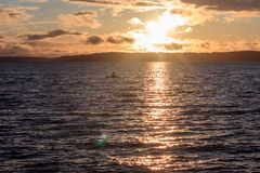 Bright sun setting over water. Through golden clouds Stock Photo