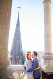Bright sun shines over wedding couple kissing. Between the white pillars on balcony Royalty Free Stock Images