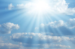 Bright sun shines among the white clouds Stock Images