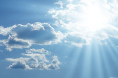 Bright sun shines among the white clouds Stock Photo