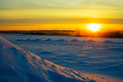 Bright sun at sunset in winter with large snow drifts. Royalty Free Stock Images