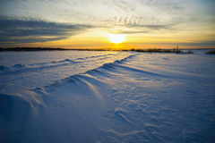 Bright sun  sunset  winter with  road and  footprints in the snow. Royalty Free Stock Image