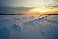 Bright sun  sunset  winter with  road and  footprints in the snow. Stock Photography