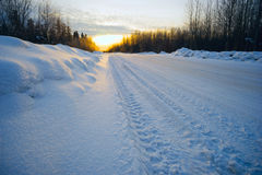 Bright sun at sunset in winter snow-covered road . Royalty Free Stock Photography
