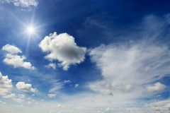Bright sun and white clouds on the background of an blue sky. Stock Photography
