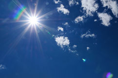 Bright sunburst with lens flare. Bright sunburst with natural lens flare and radiating rays in a blue summer sky with fluffy white clouds and copyspace Stock Photography