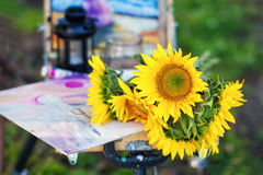 Bright sunflowers lie on an easel painter. Flowers conceptn Royalty Free Stock Photography