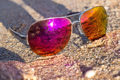 Bright sunglasses lie on the sand in the bright sun. Sea, beach sand. Bright sunglasses lie on the sand in the bright sun. Sea, beach. Accessories - sunglasses royalty free stock image