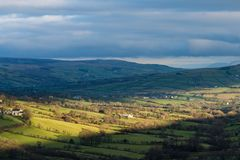 A wide beam of sunlight highlights farms and fields in the Irish landscape stock image