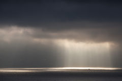 Bright sunlight goes through dark stormy clouds Royalty Free Stock Images