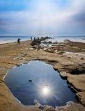 Bright sunlight illuminates sea, rocks and cliffs on Jurassic Co Stock Images