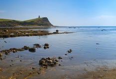 Bright sunlight illuminates sea, rocks and cliffs on Jurassic Co Stock Photography