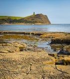 Bright sunlight illuminates sea, rocks and cliffs on Jurassic Co Stock Photos