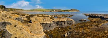 Bright sunlight illuminates sea, rocks and cliffs on Jurassic Co Stock Image