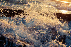 Bright sunlight passes through the splashes of sea waves. seascape Stock Photography