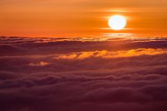 Bright sunlight reflected on a sea of clouds before sunset stock images