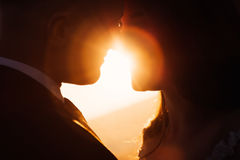 Bright sunlught shines between the lips of lovely couple.  Royalty Free Stock Image