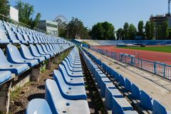 Seat in the stadium province running track and grass green field. Bright sunny day blue clear sky blue seating in the stadium grass green field and track running Stock Images