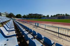 Seat in the stadium province running track and grass green field. Bright sunny day blue clear sky blue seating in the stadium grass green field and track running Stock Photos