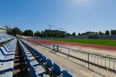 Seat in the stadium province running track and grass green field. Bright sunny day blue clear sky blue seating in the stadium grass green field and track running Royalty Free Stock Photo