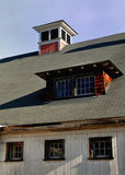 Bright sunny late fall day highlights the cupola and windows on a dirty New England white barn royalty free stock photography