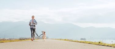 Bright sunny Morning Canicross exercises. Female runs with his beagle dog and happy smiling royalty free stock photos