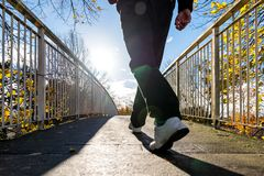 Bright sunny morning view of man walking on pedestrian bridge in british autumn stock images
