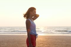 Bright Sunny summer portrait of a young beautiful brunette on the background of the sunset and the sea shore with waves. stock photography