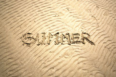 Bright sunny summer word handwritten on sand Stock Images