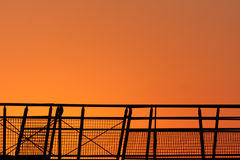 Bright sunrise. With a metal railing in the foreground in silhouette royalty free stock photography